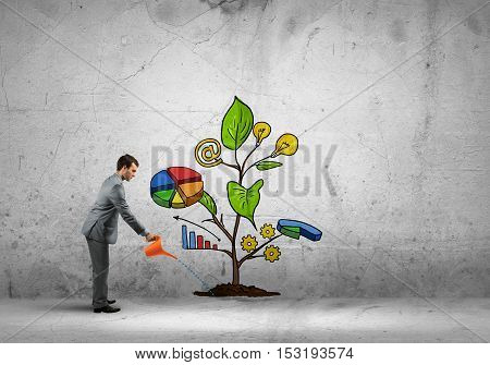 Young businessman on concrete background watering growing sprout with can