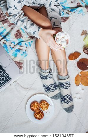 Long female feet in warm woolen socks around her is a laptop. Morning with cup.