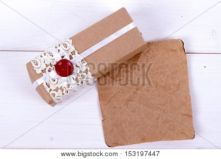 homemade gift box of kraft paper with lace and a red button and a paper peace. Gift for Valentine's day or birthday or New Year