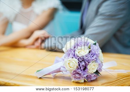Wedding flowers bouquet with newlywed couple in background