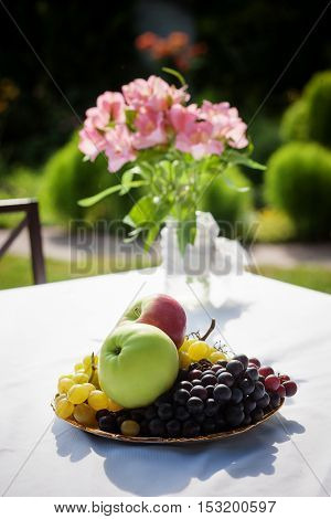 Picture of delicious fruints represented on cottage table outdoors. Beautiful terrace with small table, chair and flowers.