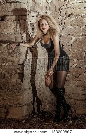 woman in leather with chains and meat in old castle. Helloween theme