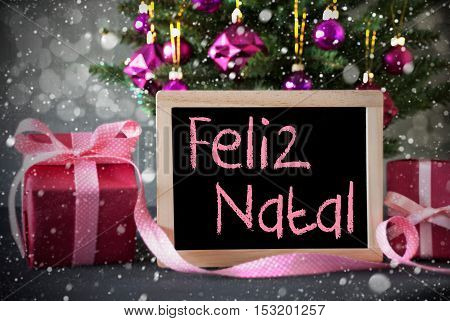 Chalkboard With Portuguese Text Feliz Natal Means Merry Christmas. Christmas Tree With Rose Quartz Balls, Snowflakes And Bokeh Effect. Gifts Or Presents In The Front Of Cement Background.