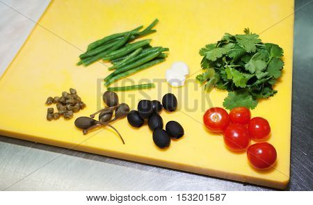 Vegetables represented on table in kitchen: tomatoes, olives, etc. Food ingredients on table board . Closeup shot.