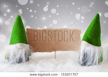 Christmas Greeting Card With Two Green Gnomes. Sparkling Bokeh And Noble Silver Background With Snow. Copy Space For Advertisement
