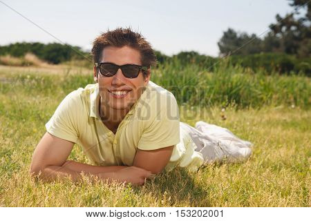 Young man laying on the grass in sunglasses and smiling at the camera. Handsome man laying on the green grass.
