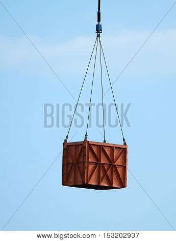 Metal cargo container is attached by cable to the aircraft for transportation