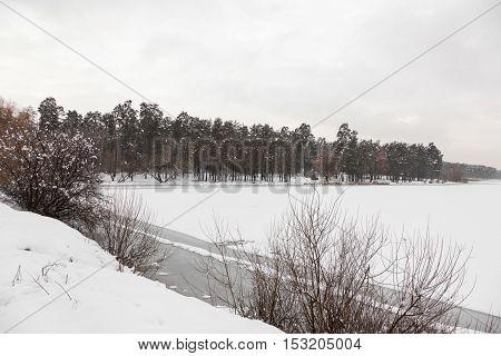 Frozen lake in the forest winter landscape