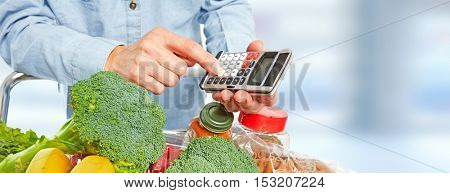 Woman hands with grocery food and calculator.