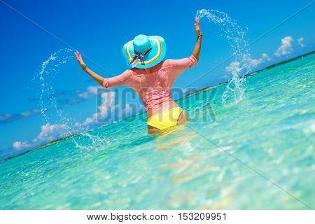 Woman in bikini having fun on the beach in Exuma, Bahamas