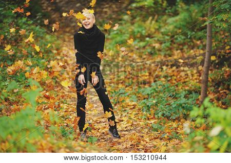 Cute cheerful blonde posing in autumn forest under the falling maple leaves.
