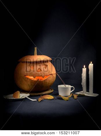 Pretty good halloween pumpkin drinking coffee by candlelight