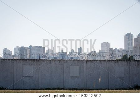 Barbed wire wall with urban scene and buildings behind