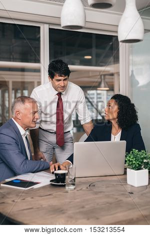 Three diverse businesspeople talking together over a laptop while working at a table in an office boardroom