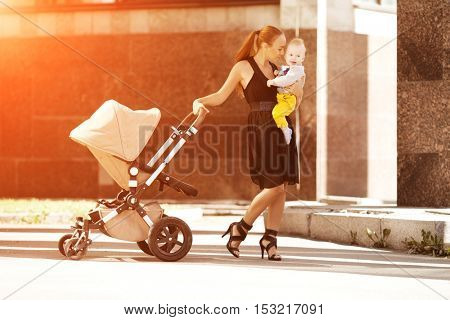 Fashionable modern mother on a city street with a pram. Young mother walks with a 