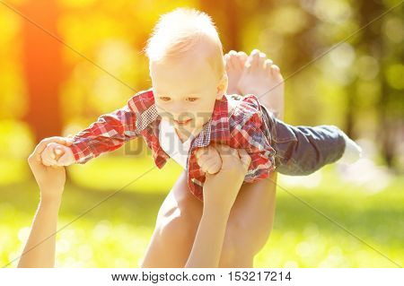 Cute little baby in summer  park with mother  on the grass. Sweet toddler and mom  outdoors. Smiling emotional kid with mum on a walk. Smile of a child