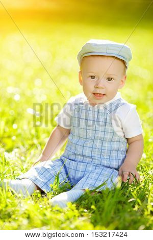 Cute little baby in summer  park on the grass. Sweet baby outdoors. Smiling emotional  kid on a walk. Smile of a child