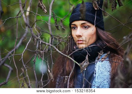 Serious young brown-eyed brunette with long hair in a scarf and hat in the Park among the bare branches of trees in close-up.