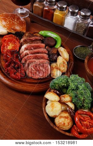 fresh roast bbq beef meat ribeye steak on wooden plate served with tomato juice in wooden cup, boiled broccoli, baked tomatoes potatoes, with white bun, and red wine glass on light walnut wooden table