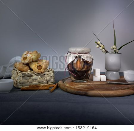 jar of plum jam, fresh bread rolls on wooden table on gray background