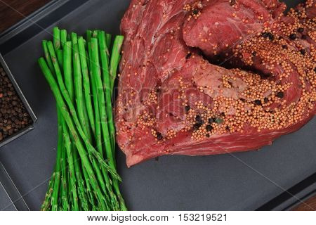 meat raw beef fillet chunk on black tray asparagus on wooden table allspice pink white black green peppercorn stainless cutlery knife fork
