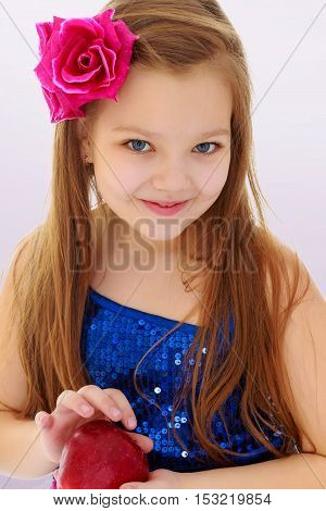 Beautiful little long haired girl, with rose in hair, holding an Apple . close-up.On a purple background.