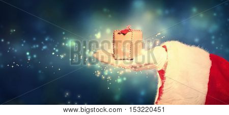 Santa Claus holding a Christmas gift box in snowy night