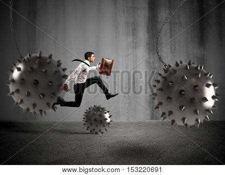 Businessman between fierce spiky balls that hinder