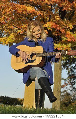 Beautiful Asian woman playing guitar outside during fall season