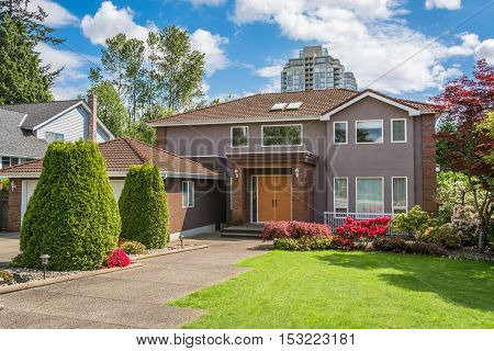 Residential house with concrete pathway over front yard lawn. Single family house in urban area on cloudy sky background.