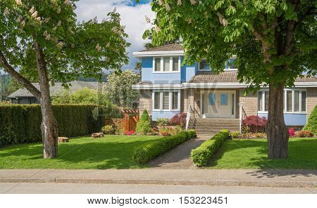 Beautiful family house with green lawn on front yard in suburban area of Vancouver Canada