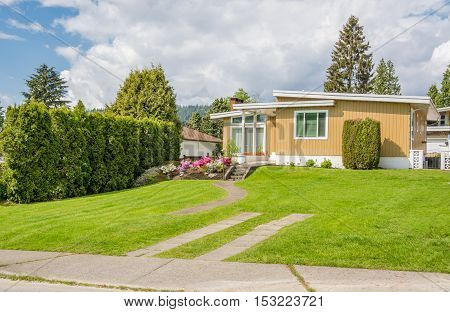 Beautiful family house with parking spot on green lawn of the front yard. Residential house in suburban area of Vancouver Canada