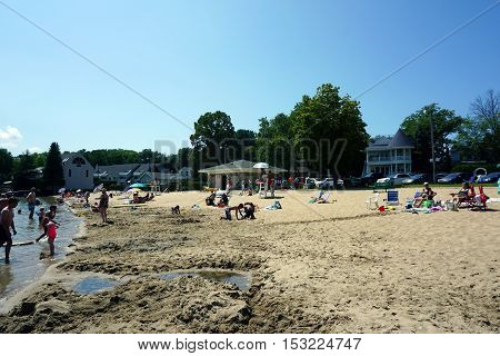HARBOR SPRINGS, MICHIGAN / UNITED STATES - AUGUST 3, 2016: People enjoy swimming, playing, and sunbathing at the Zorn Park Public Beach near downtown Harbor Springs.