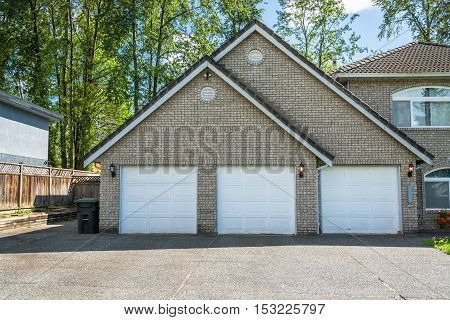Garage of big residential house with three parking places and three doors. Garage with gabble roof and concrete driveway in front