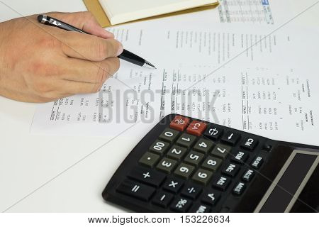 Hand of accountant checking financial document with calculator and notebook.
