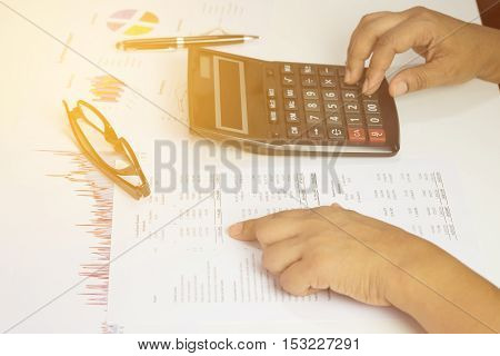 Hand of accountant checking financial document with sunlight