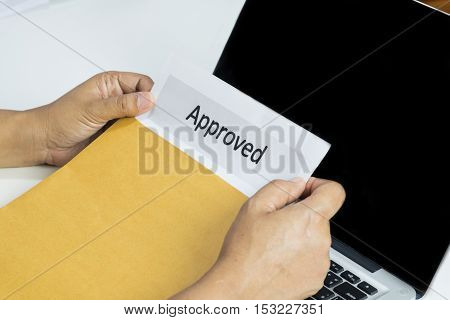 Hand Of Businessman Opening Approved Document From Envelope