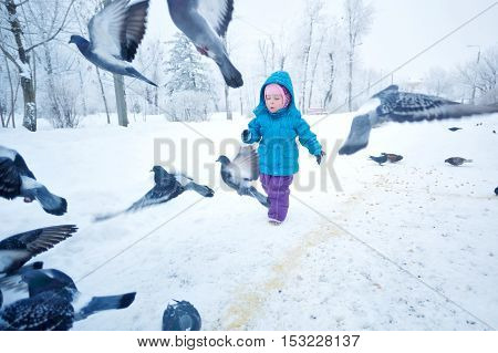 Cute little girl on a walk in a winter park. The kid runs around and frightening doves. Childhood Joy.