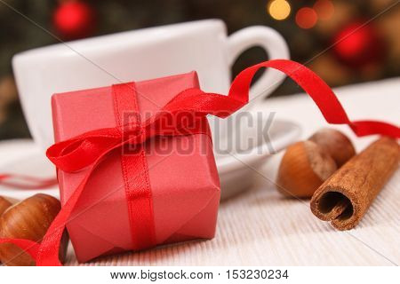 Wrapped Gift, Cup Of Tea Or Coffee And Christmas Tree With Lights In Background