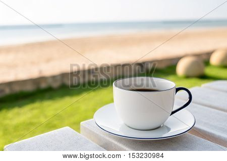 Close up white coffee cup on wood table and white sand beach over blue sky and sea view of sunset or sunrise background - Solf Focus
