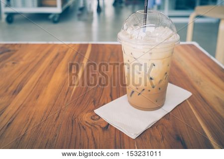 Cold coffee in plastic cup on a wooden table - vintage style (soft focus)
