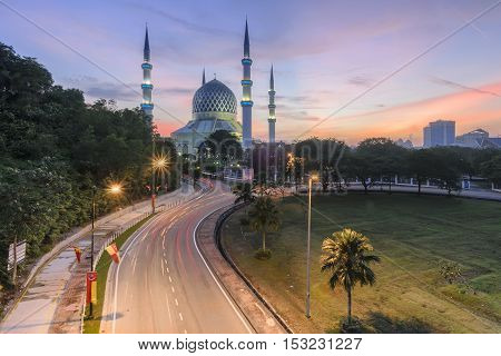 View of Shah Alam Mosque with blue skies and white clouds during sunrise.