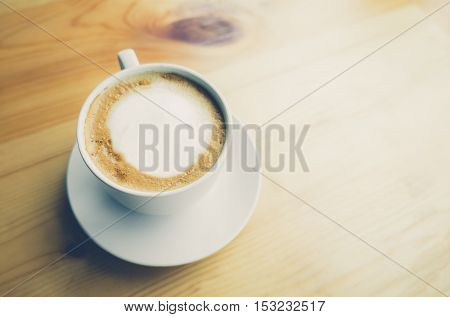 Cup of hot latte coffee on brown wooden table. Top view