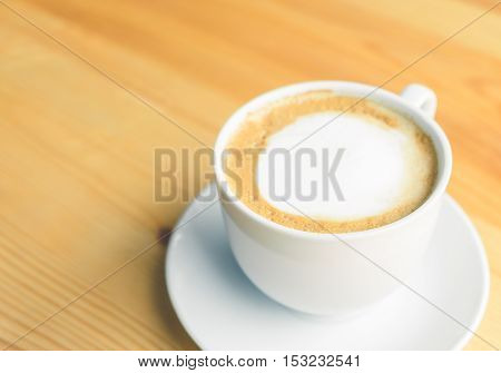 Hot latte in white coffee cup on wooden table background.