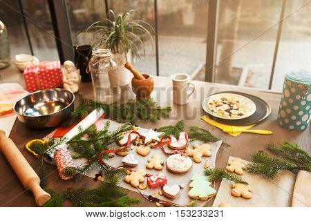 Table with Christmas spirit. Kitchen of family actively preparing for winter holidays. Gingerbread cooking, culinary, celebration concept