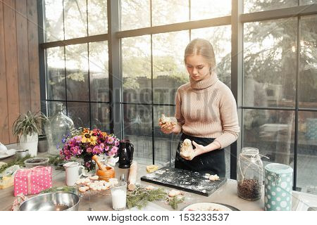 Young woman cooking at kitchen. Attractive confectioner preparing dough for cake, pie or cookies. Culinary classes, pastry cooking, homemade cuisine concept