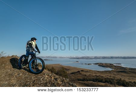 Fatbike also called fat bike or fat-tire bike - Cycling on large wheels. Traveller cyclist stands on the top of the mountain. He is resting on a trip looking at the sunset and sitting on the bike.