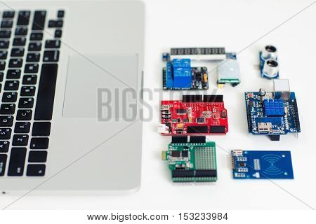 Close-up of colorful electronic components near laptop keyboard. Electronic shields for engineering and technology development
