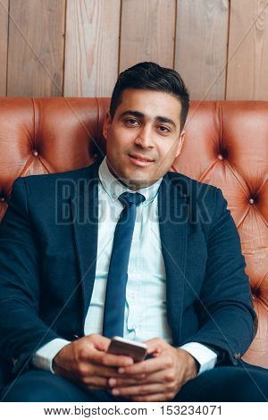 Portrait of rich self-made businessman looking at camera, free space on wooden background. Success and prosperity concept.