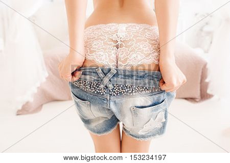 Sexy woman lowered denim shorts to show buttocks. Seductively undressing girl, sex, passion, temptation concept